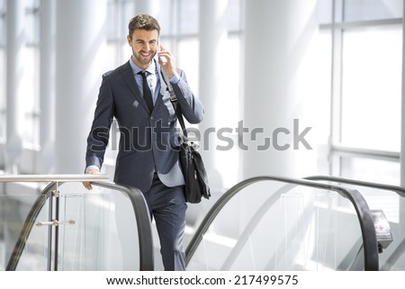 Businessman on the phone smiling at the escalator - stock photo
