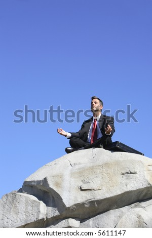 Businessman on top of rock meditating - stock photo
