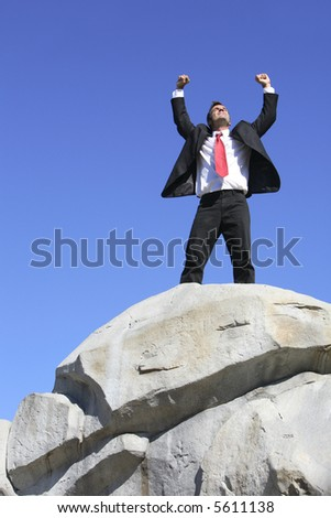 Businessman on top of rock with arms outstretched - stock photo