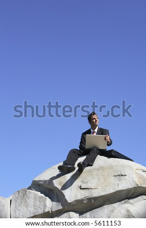 Businessman on top of rock with laptop computer - stock photo