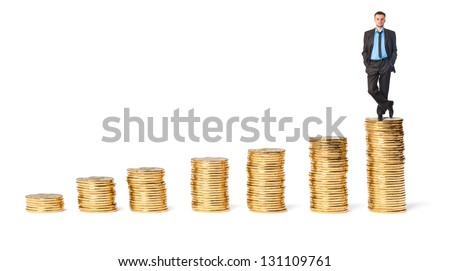 Businessman on top the gold coins on a white background