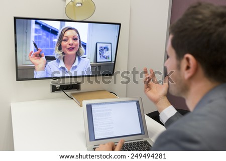 Businessman on video conference with her colleague in office job - stock photo
