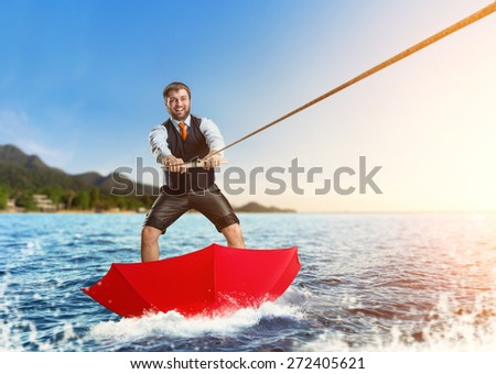 Businessman on water skis in umbrella - stock photo