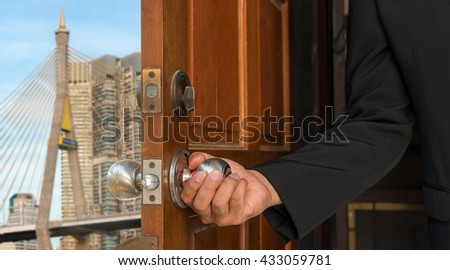 businessman open door to blur background of cityview and bridge on blue sky - can use to display or montage on product - stock photo