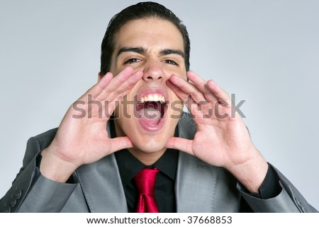 Businessman open hands shout to camera on gray background - stock photo