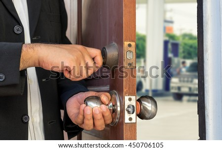 businessman open the door by key on blur gas station view - can use to display or montage on products or concept about save energy or oil - stock photo
