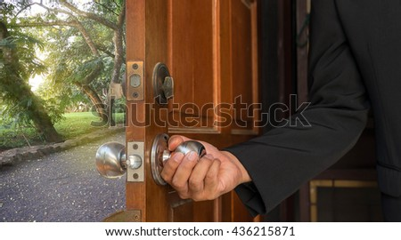 businessman open the wood door to garden and sun light - can use to display or montage product or concept of begin a new way - stock photo