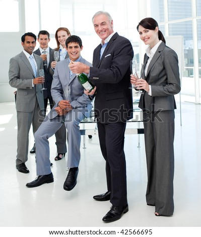 Businessman opening a bottle of Champagne to celebrate a success in the office - stock photo