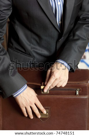 Businessman opening elegant brown leather briefcase - stock photo