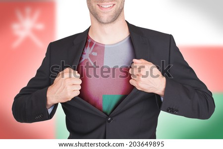Businessman opening suit to reveal shirt with flag, Oman