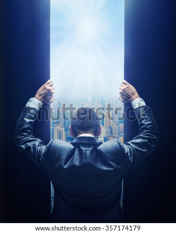 Businessman opening the gate to the city - stock photo