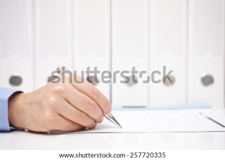 Businessman or accountant is signing document with binders in background - stock photo