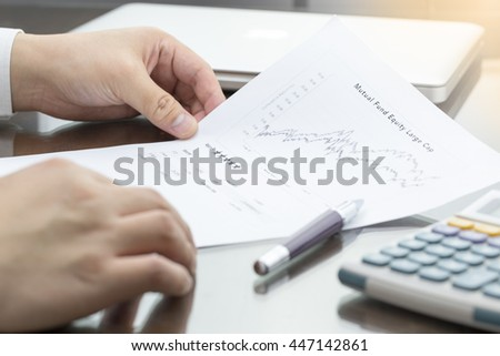 Businessman or fund manager review Mutual Fund information with performance line graph and benchmark with pen, calculator and computer laptop.
