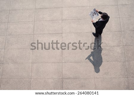 Businessman or manager reading newspaper article, view from above - stock photo