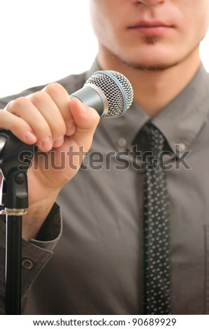 businessman or singer in grey coat witn neck tie holding microphone in his hand ready to perform - shallow DOF with focus on the microphone - stock photo