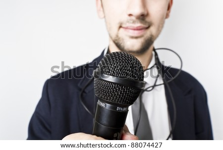 Businessman or Singer in suit. Microphone in his hand ready to perform. - stock photo