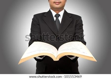 Businessman or teacher reading from a book