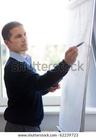 Businessman or teacher writing on whiteboard. - stock photo