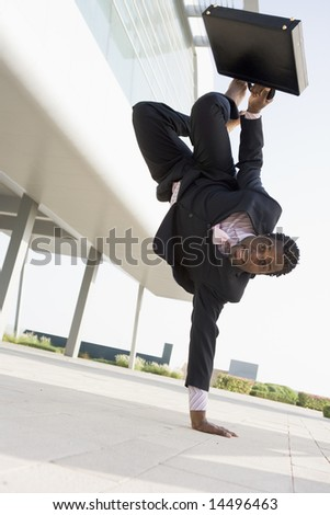 Businessman outdoors by building standing on one hand smiling - stock photo