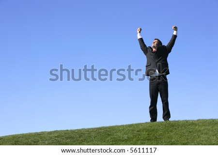 Businessman outdoors celebrating with arms outstretched