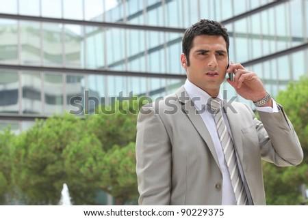 Businessman outdoors talking on phone - stock photo