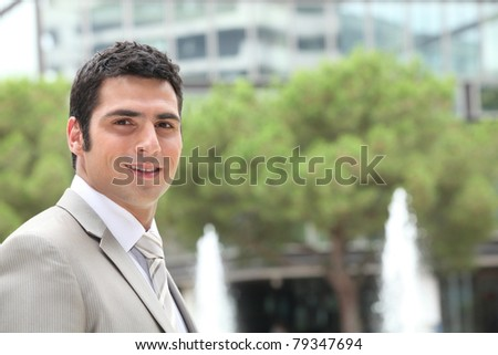 Businessman outside an office building with fountains - stock photo
