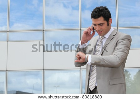 Businessman outside looking at watch - stock photo