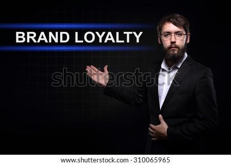 Businessman over black background presenting Brand loyalty - stock photo