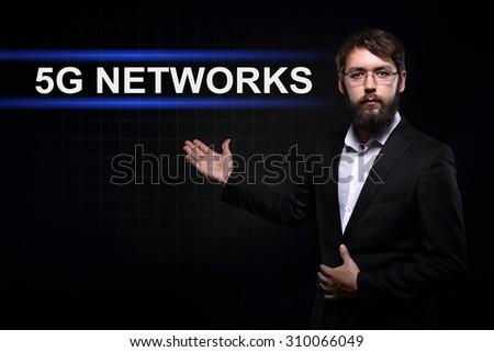 Businessman over black background presenting 5G network - stock photo