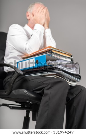 Businessman overloaded holding his face with his hands - stock photo