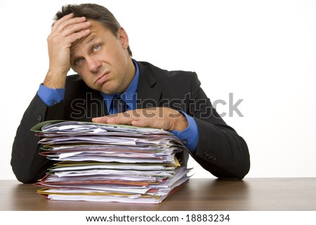 Businessman Overwhelmed By Paperwork - stock photo