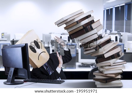 Businessman overworked with a pile of books in the office - stock photo
