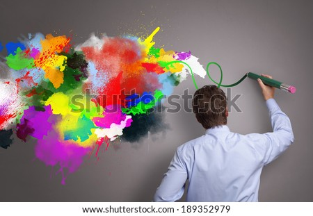Businessman painting abstract colorful design on gray background concept for  business creativity, imagination and inspiration - stock photo
