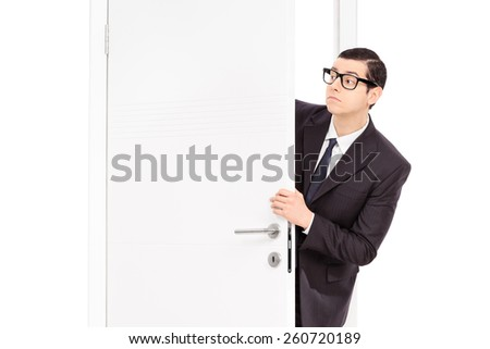 Businessman peeking through an opened door isolated on white background - stock photo