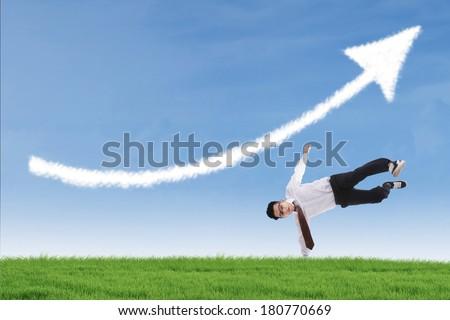 Businessman perform success move under up arrow cloud outdoor - stock photo