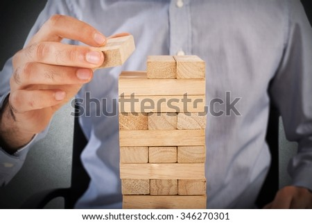 Businessman playing at a wood brick building - stock photo