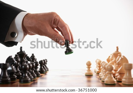 businessman playing chess game selective focus back makes first move - stock photo