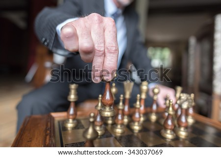Businessman playing chess, strategy concept
