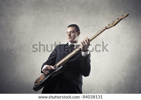 Businessman playing guitar - stock photo