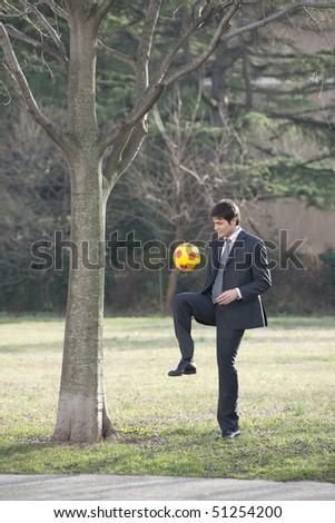 Businessman playing soccer/football - stock photo