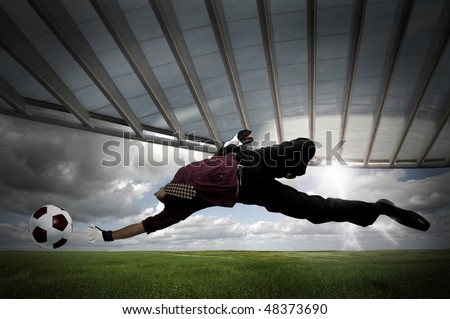 Businessman playing soccer outdoors in a green field - stock photo