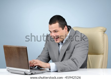 Businessman playing video game at working hours on gray background