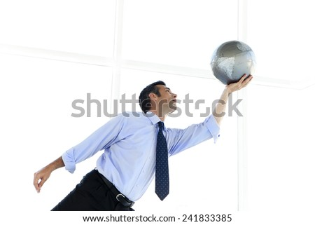 Businessman playing with a globe