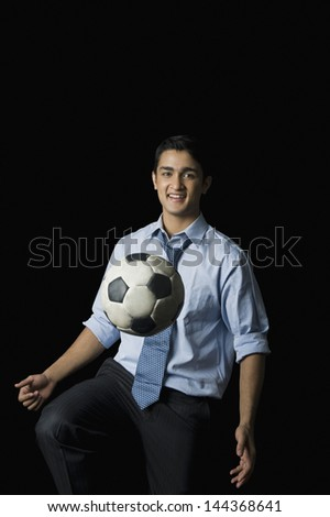 Businessman playing with a soccer ball - stock photo