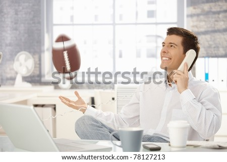 Businessman playing with football office while on landline call, laughing.? - stock photo