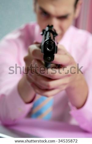 Businessman point his handgun to camera, wallpaper background - stock photo