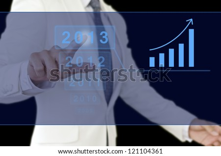 Businessman point to 2013 chart. This photo represents a success in 2013.