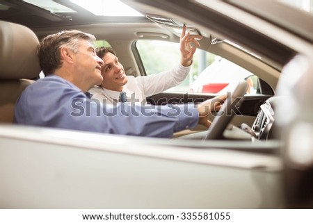 Businessman pointing a car interior at new car showroom - stock photo