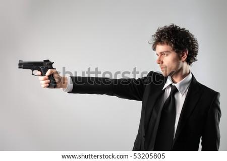 Businessman pointing a gun at something - stock photo