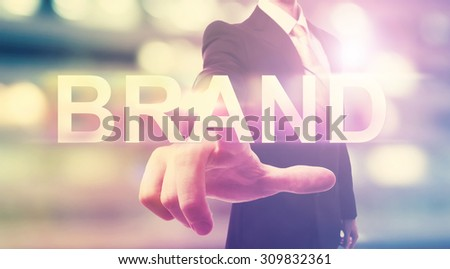 Businessman pointing at BRAND on blurred city background - stock photo